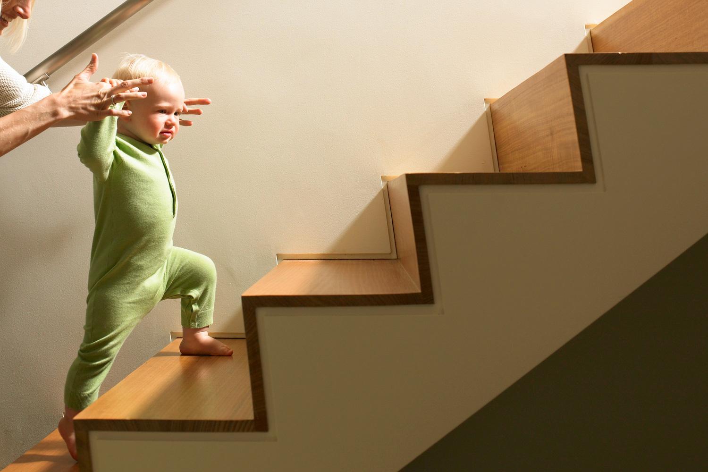 Eine Mutter hilft ihrem Baby dabei, die Treppe hochzusteigen. Thema: Eltern werden