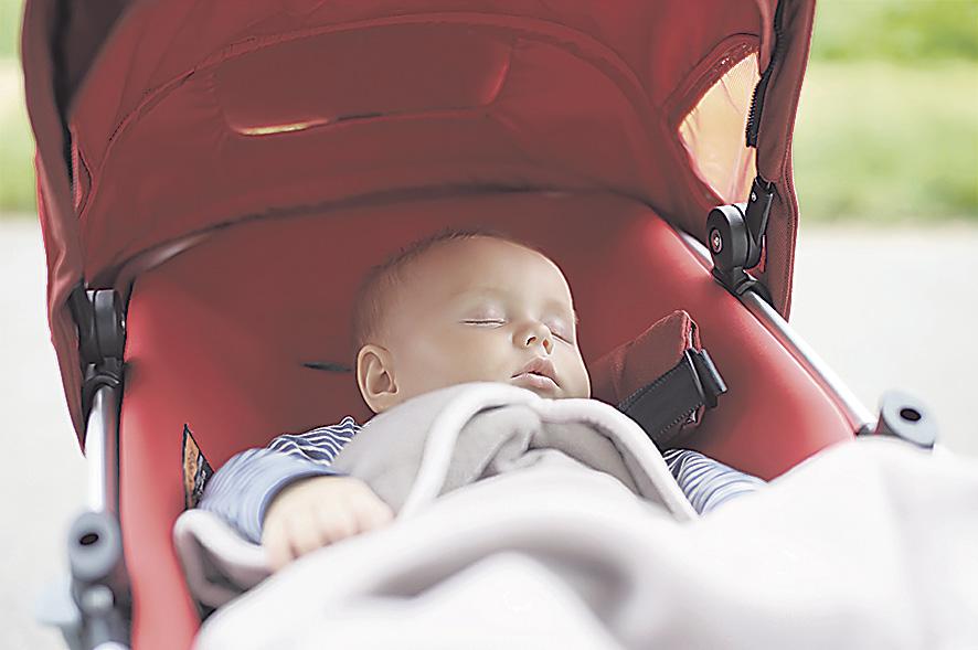 Ein Baby schläft in seinem Kinderwagen