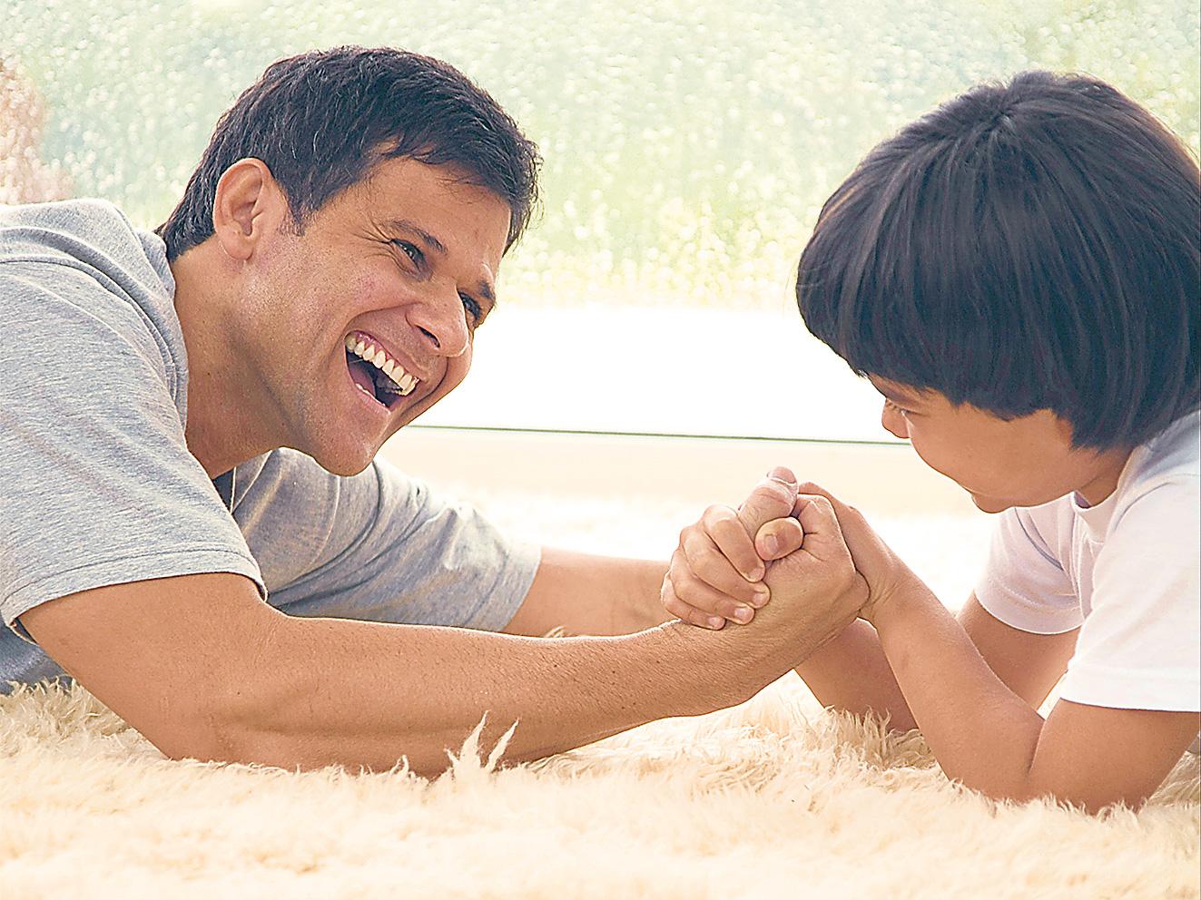 Vater und Sohn beim spielerischen Armdrücken. Thema: Vater-Sohn-Beziehung