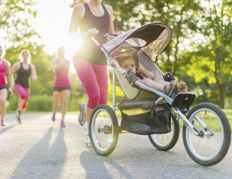 Mutter, die mit ihrem Kind im sportlichen Kinderwagen joggen geht