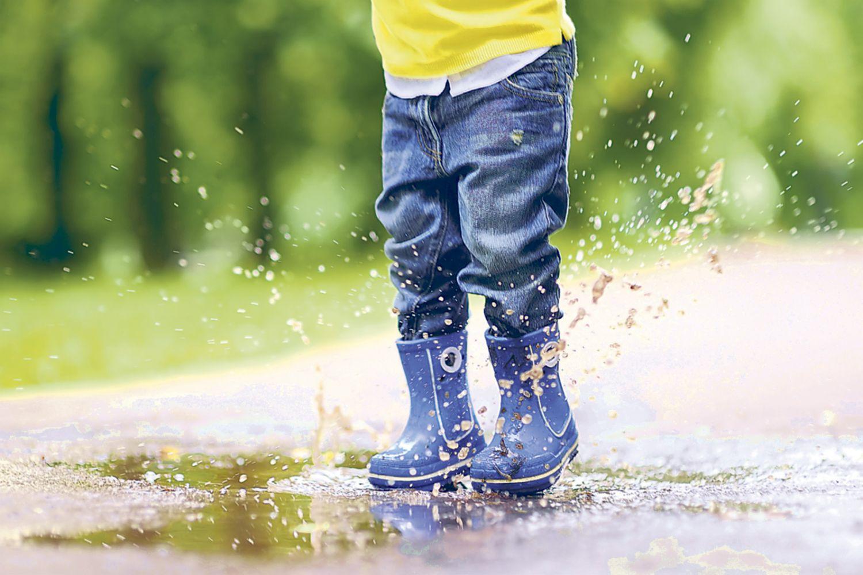 Kind steht mit Gummistiefeln in einer Pfütze. Thema: Babys erste Schuhe