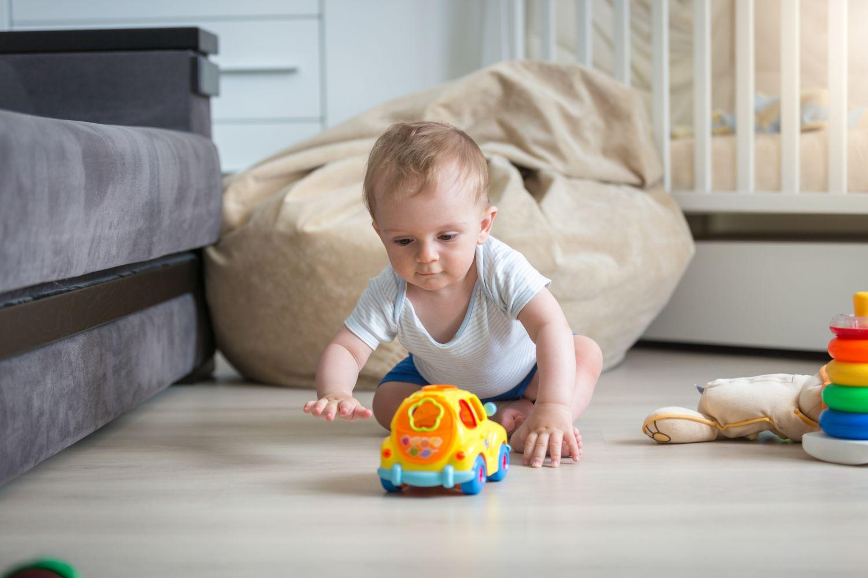 Ein Kleinkind krabbelt über den Boden zu einem Spielzeug. Mit der richtigen Erstlingsausstattung ist für alles gesorgt.