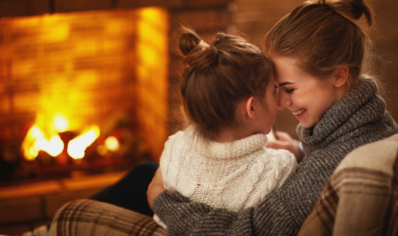 Mutter und Tochter kuscheln vor dem Kamin. Thema: Tipps zum Hauskauf