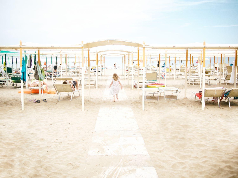 Kleines Mädchen am Strand zwischen Sonnenstühlen und -schirmen