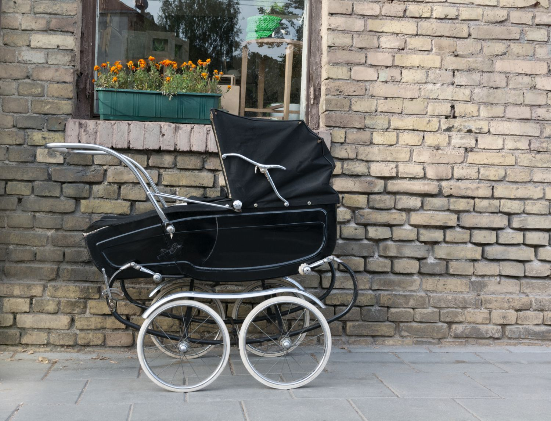 Ein altmodischer Kinderwagen. Viele Eltern stehen vor der Qual der Wahl, wenn es um Transportmöglichkeiten für ihr Baby geht. Kinderwagen oder Tragetuch?