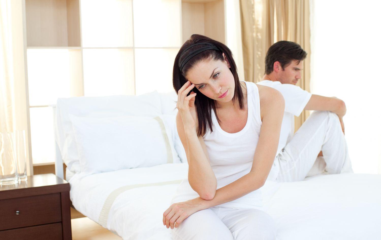 Ein schlecht gelauntes Paar sitzt mit den Rücken zueinander auf dem Bett. Ein unerfüllter Kinderwunsch kann die Beziehung auf die Probe stellen.