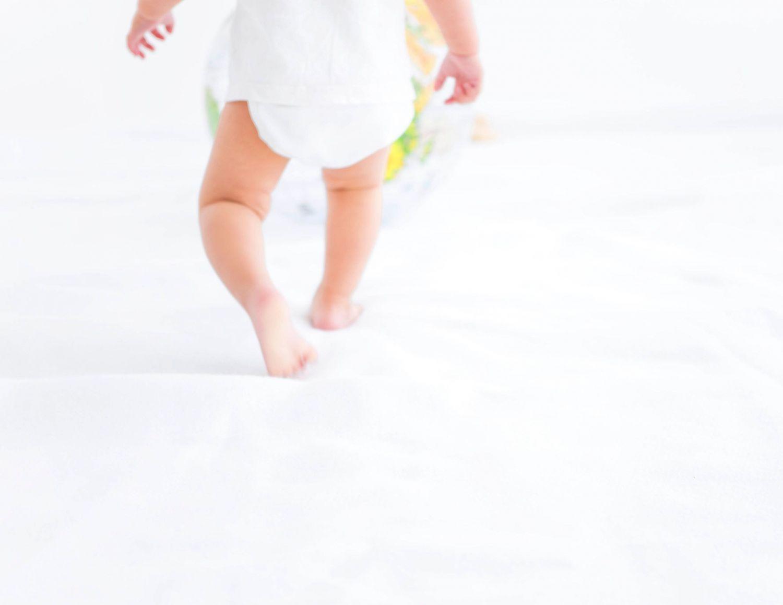 Ein Kleinkind mit Windel läuft umher. Thema: Windelwahl