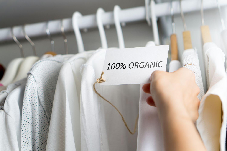Weiße Kleider an Bügeln im Kleiderschrank. Gesunde Babykleidung ist ein heißes Thema