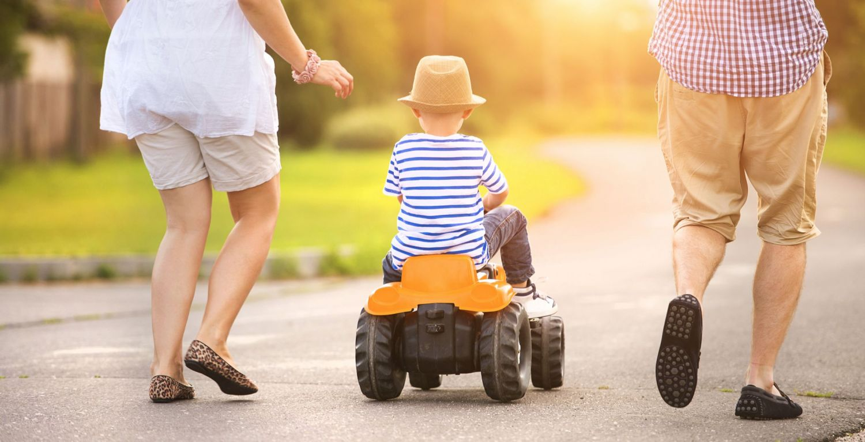 Ein Kind auf einem Spielzeug-Trecker zwischen seinen Eltern
